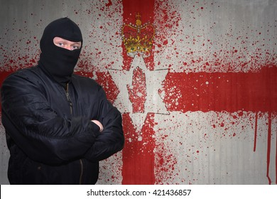 dangerous man in a mask standing near a wall with painted national flag of northern ireland