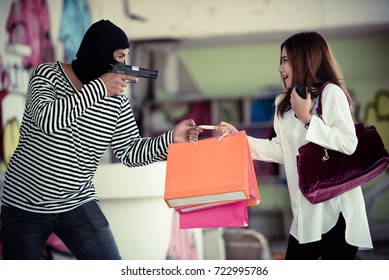 Dangerous man or masked robber with gun attacking scared young woman and stealing her shoulder bag and shopping bags on the footpath.