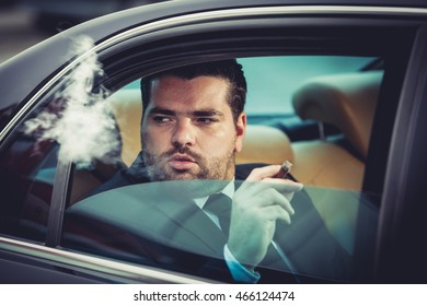 Dangerous man smoking  in the back seat of a car