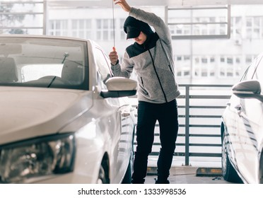 Dangerous man is standing next to a car and trying to rob it with pry bar