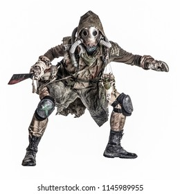 Dangerous, mysterious post apocalypse creature, global ecological disaster survivor in tatter, gas mask, wearing mystical amulet, crouching with bloody machete in hands isolated on white studio shoot