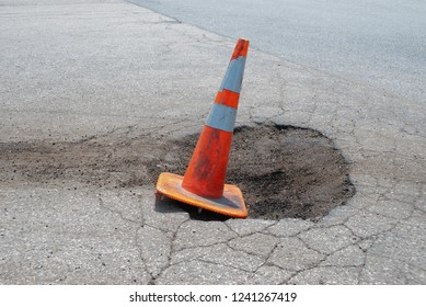 Dangerous pothole marked by an orange cone