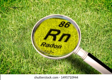 The dangerous radioactive radon gas under the ground - concept image with periodic table of the elements, magnifying lens and green grass area on background.