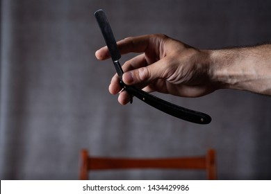 Dangerous razor in the hand of a man hairdresser. On a gray background.