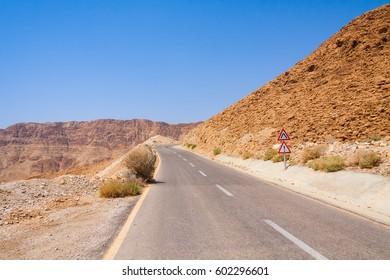 Dangerous road sign on steep turn of ascend highway in Judean desert with Dead Sea in background. Metzoke Dragot, Israel.