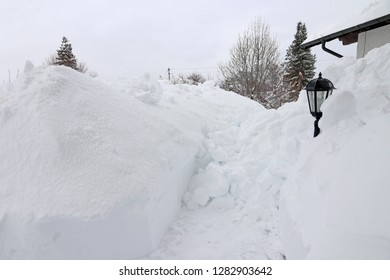 A dangerous roof avalanche has fallen from the roof of a house onto the sidewalk.