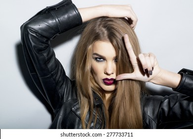 Dangerous sexy young blonde woman with bright make up in black leather jacket looking forward stanging on light grey background closeup copyspace, horizontal picture