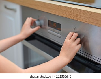 Dangerous situation in the kitchen. Child playing with electric oven.
