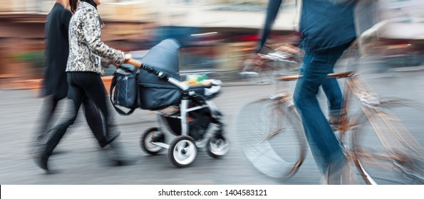 Dangerous situation on the road. Cyclist a second before a collision with a pram.  Intentional motion blur