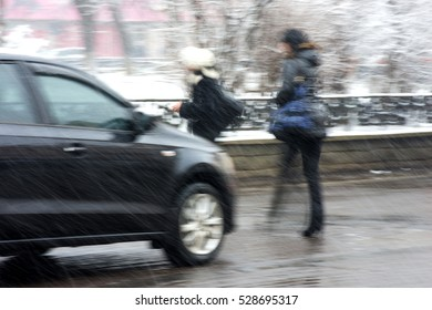 Dangerous situation on zebra crossing with pedestrian and a car. Intentional motion blur