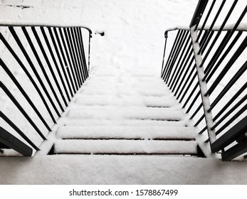 Dangerous slippery stairs and old handrail in the winter in the snow.