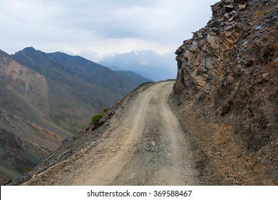 Dangerous steep and shallow unpaved road in mountains
