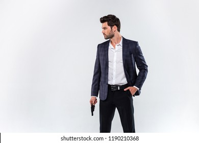 Dangerous style. Handsome young man looking away and holding a gun while standing against white background