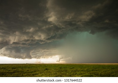A dangerous supercell storm containing torrential rain and large hail emits a green glow in the sky.