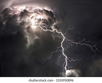 Dangerous towering summer monsoon storm clouds with large branched lightning striking to earth.