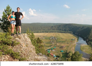 A dangerous trick without insurance on the edge of the abyss. The young man raised his girlfriend on the very edge of a high cliff. All this takes place against the background of a wonderful landscape