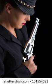 Dangerous woman in black with silver handgun and stylish hat