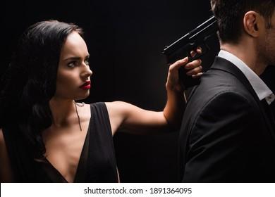 dangerous woman in dress holding gun near man in suit isolated on black