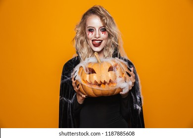 Dangerous woman wearing black costume and halloween makeup holding carved pumpkin isolated over yellow background