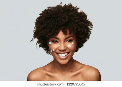Dangerously beautiful. Attractive young African woman looking at camera and smiling while standing against grey background
