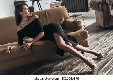 Dangerously beautiful. Attractive young woman in elegant black dress with a deep slit looking away while sitting on the sofa