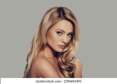 Dangerously beautiful. Attractive young woman with long blond hair looking at camera while standing against grey background