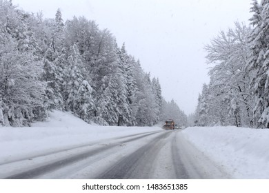 dangerously snow-covered alpine road with oncoming snowplow, seen from the cockpit of a car, blurred because of the snowfall
