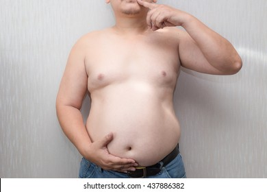 The Dangers of Belly Fat. Obese Man in Jeans Squeeze the Belly Fat.  man with a big belly and more likely to Clog arteries.  Man at risk for diabetes.  Obese people with diabetes.  Belly Fat. Diet.