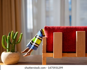 Dangling doll feet of a black skinned doll. On a red couch. Potted cactus on the floor. Wearing african print pants. Curtains and window in the background. Room for copy.