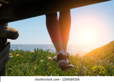 Dangling feet in shoes, woman sitting on beach