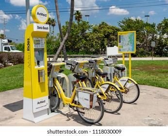 DANIA BEACH, FLORIDA, USA - JUNE 21, 2018: AvMed Rides self-service bicycle rental station, yellow