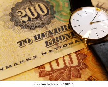 Danish 200 and 100 Kroner bills together with watch