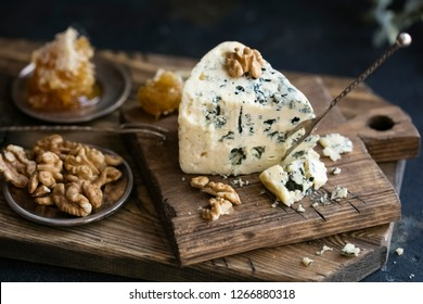 Danish blue cheese on a wooden board with walnut kernels. dark background