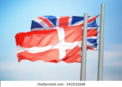 The Danish and British flags against the background of the blue sky