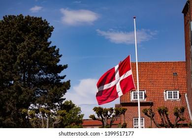 The Danish flag Dannebrog on half pole symbolizing death or christian holiday