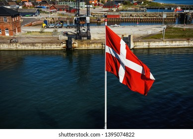 Danish flag at ferry port in Denmark, view from a departing ship.