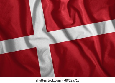 The Danish flag flutters in the wind. Colorful, national flag of Denmark. Patriotism, a patriotic symbol.