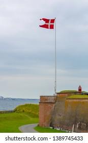 Danish flag near Kronborg castle in Denmark. Danish flag near the famous Kronborg castle on the coast of the sea. Danish harbour of Helsingor with Kronborg castle. Castle on the shore in Helsingor