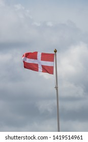 A Danish flag on a flag pole blowing in the wind