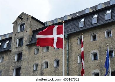 Danish flag waving with the Admiral Hotel on the background, Copenhagen, Denmark