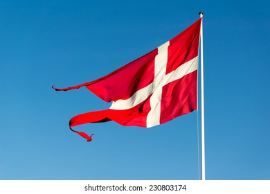 Danish flag waving in strong wind against blue sky