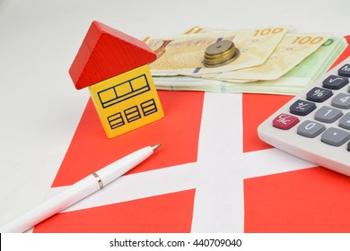 Danish Kroner notes and coins, with a house, calculator to represent property finance.
