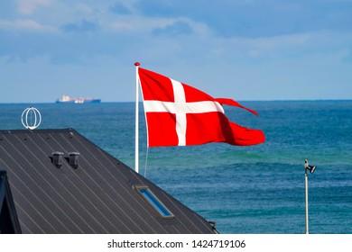 The Danish national flag Dannebrog in the wind on the North Sea coast