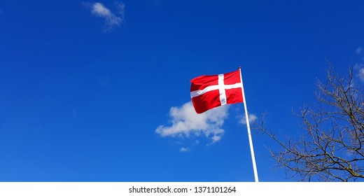 Danish red and white flag flying in the blue sky