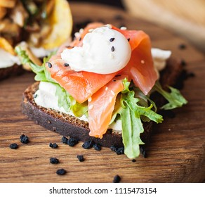 Danish Smorrebrod with red salmon fish and egg on wooden board