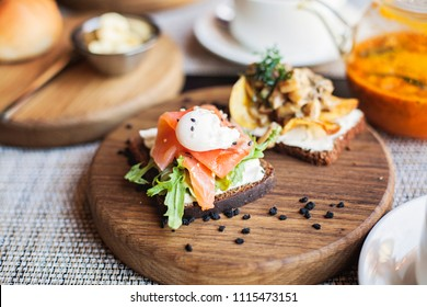 Danish smorrebrod sandwich with salmon fish and egg on wooden board. Restaurant food