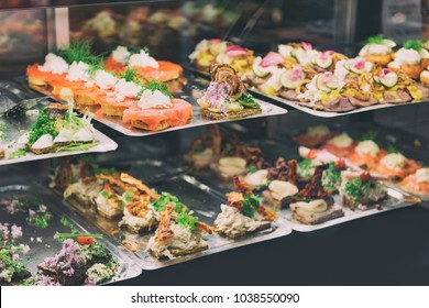Danish smorrebrod traditional open sandwich at Copenhagen food market store. Many sandwiches on display with seafood and meat, smoked salmon.