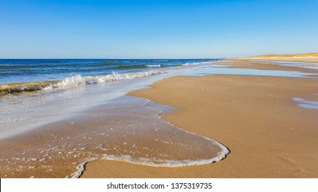 Danish west coast beach shore with waves from the ocean, blue sky and soft beach sand - no garbage clean beach.
