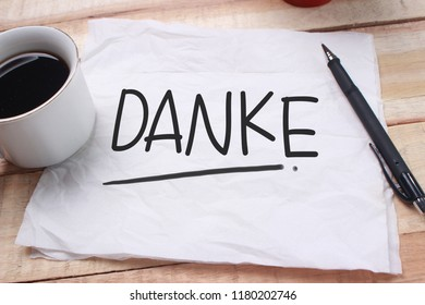 Danke, German thank you words letter, written on piece of memo paper. Motivational business typography quotes concept