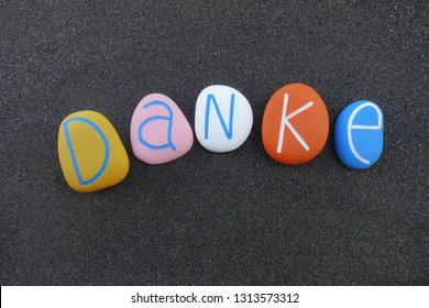 Danke, german word meaning thank you  composed with colored sea stones over black volcanic sand